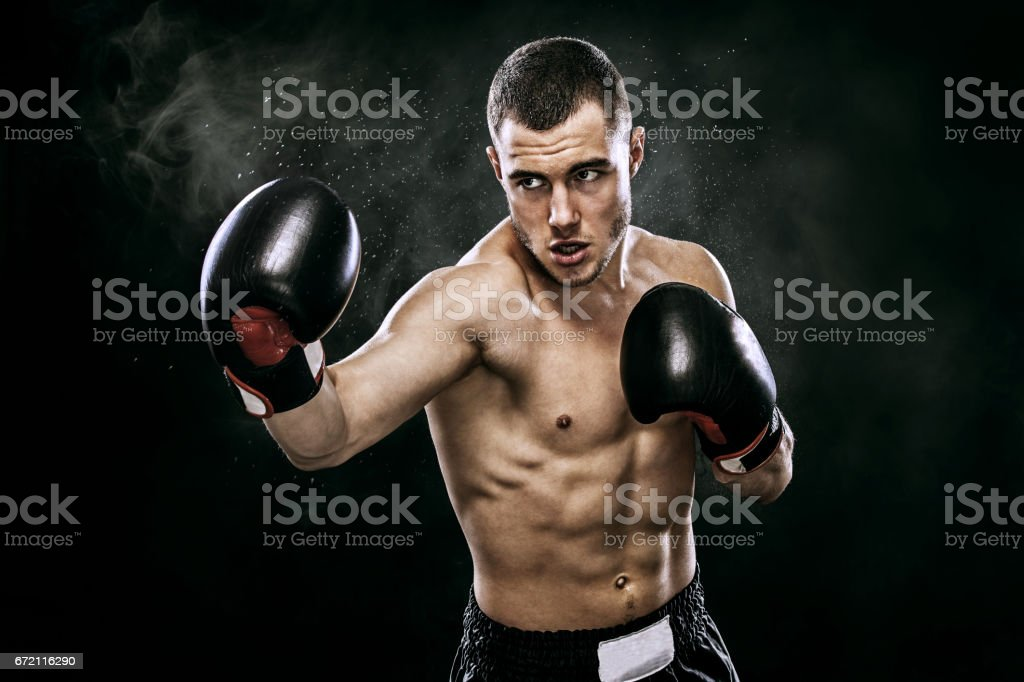 Sportsman muay thai boxer fighting in gloves in boxing cage. Isolated on black background with smoke. Copy Space. stock photo