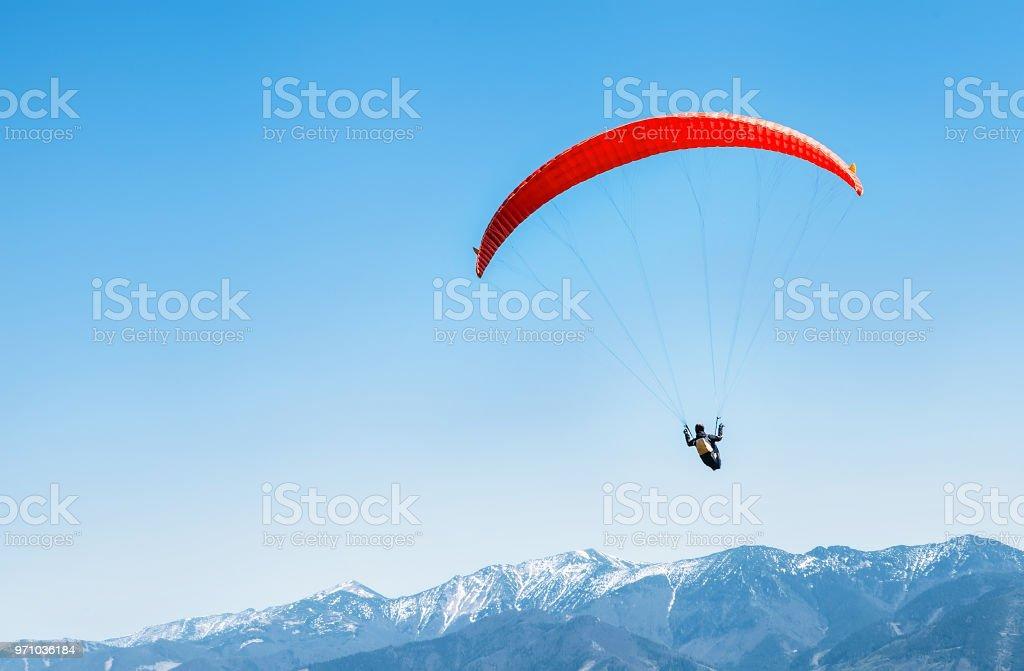 Sportler auf roten Gleitschirm über die verschneiten Berggipfel – Foto