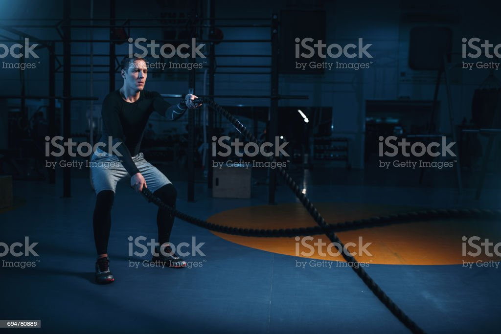 Sportsman on training, workout with battle ropes stock photo