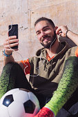 attractive sportsman putting on earphones to make a video call with his smart phone, concept of technology and urban sport lifestyle in the city