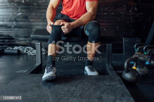 Unrecognisable cropped sportsman putting on a knee sleeve at the gym.