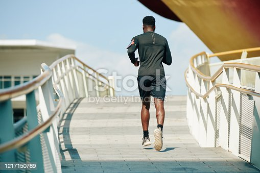 Fit young African-American sportsman running up the street