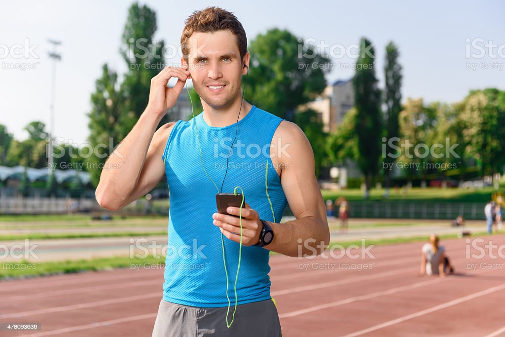 Sportsman standing with mobile phone on stadium stock photo