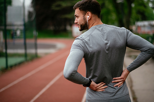 Sportsman suffering from backache at park outdoors. Back Pain. Sport injury