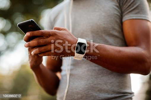 African-American male with smart watch and headphones texting messages on mobile phone during jogging session.