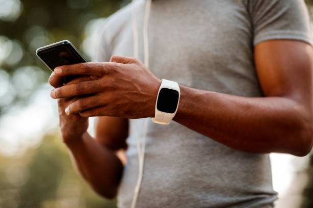 Sportsman texting on smartphone African-American male with smart watch and headphones texting messages on mobile phone during jogging session. fitness tracker stock pictures, royalty-free photos & images