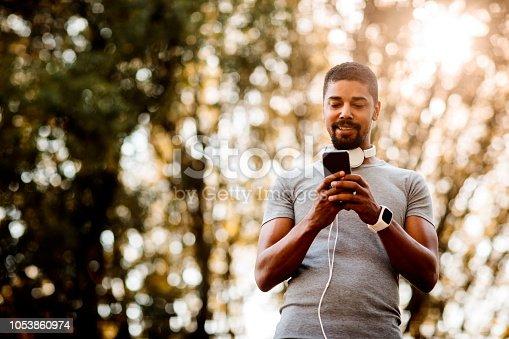 istock Sportsman texting on smartphone 1053860974