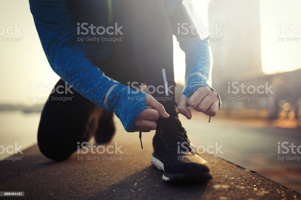 Sportsman tying shoelaces after jogging exercises stock photo