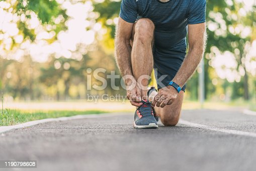 Athletic senior sportsman Tying shoelaces