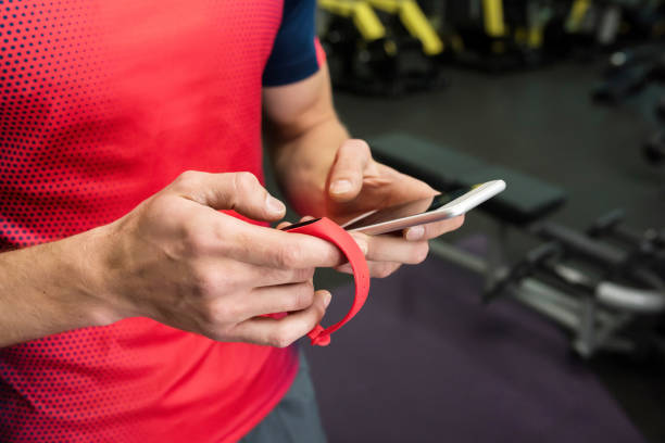 Sportsman using Fitness Device in Gym Closeup of strong male hands setting up fitness bracelet checking data on smartphone while working out in modern gym, copy space fitness tracker stock pictures, royalty-free photos & images