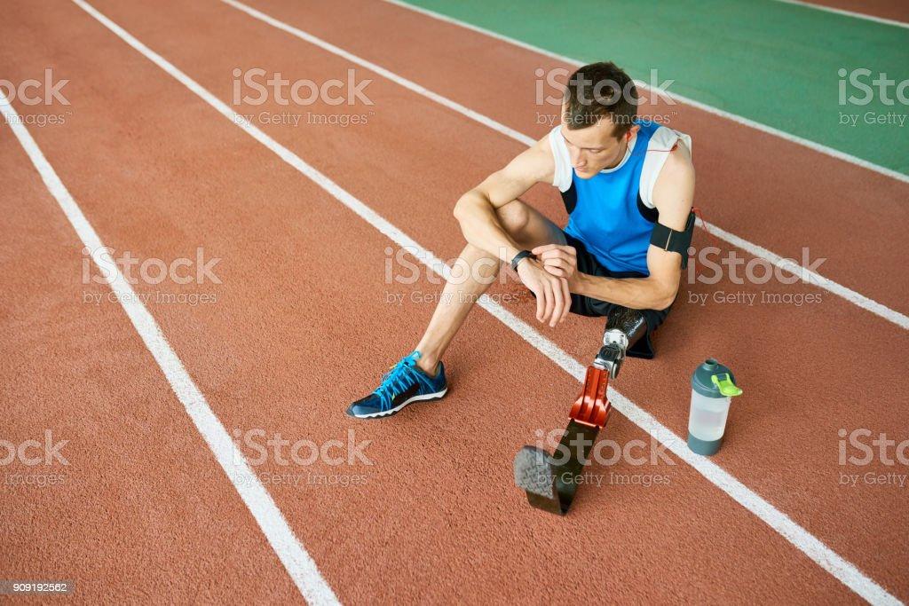 Sportler mit Artifitial Bein sitzen im Stadion – Foto