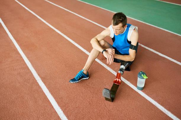 sportif avec jambe artificiel assis sur le stade - membre photos et images de collection