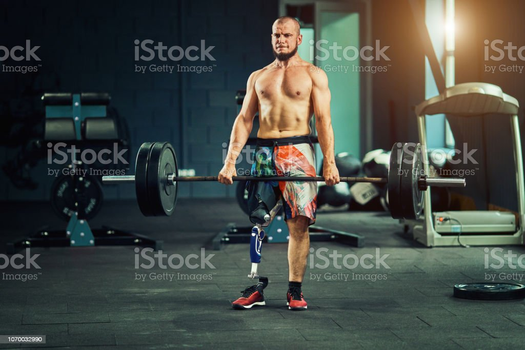 Sportsman with prosthesis working out in gym stock photo