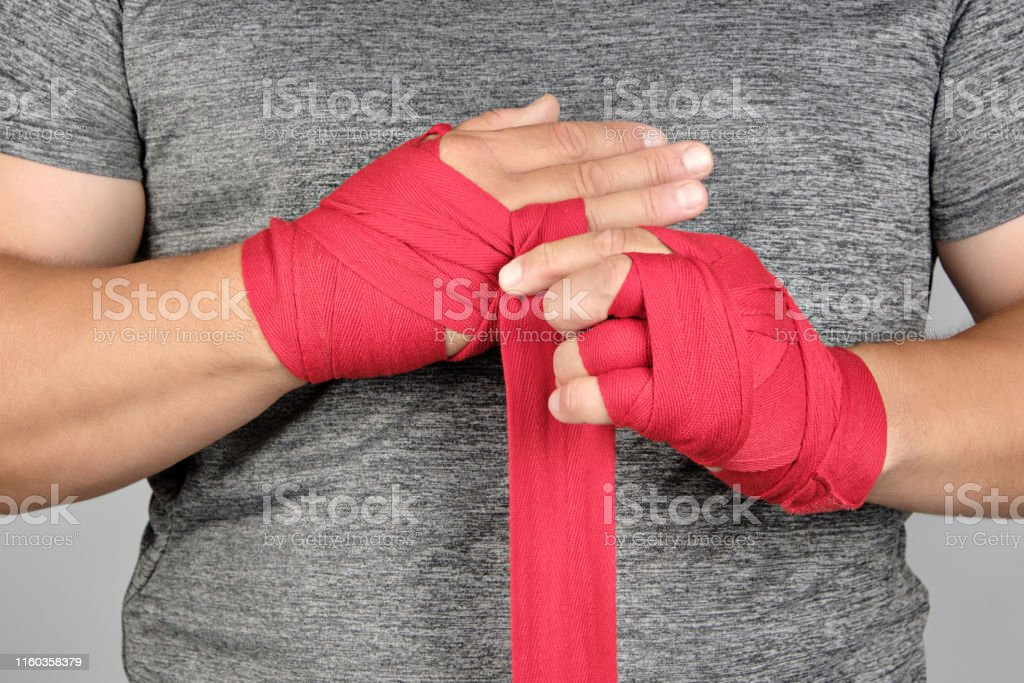 sportsman's hands wrapped in a red elastic sports bandage, close up