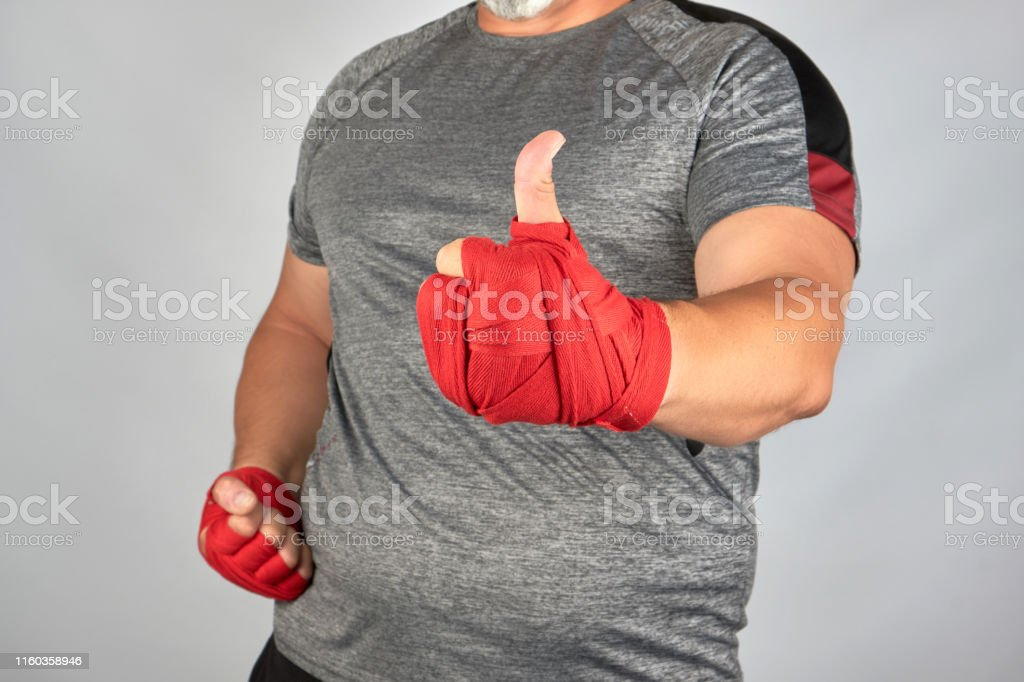 sportsman\'s hands wrapped in red elastic sports bandage show a like...