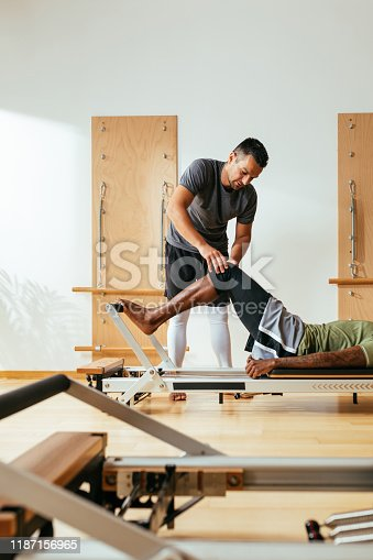 Sportsman doing reformer pilates exercise with his trainer.