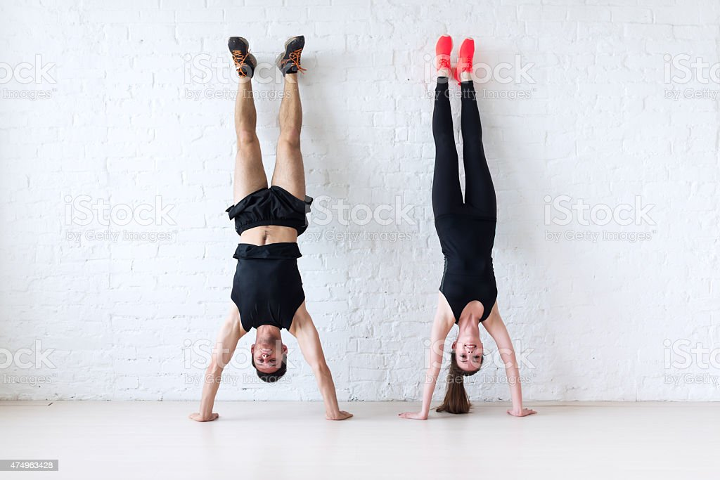 sportsmen woman and man doing a handstand against wall concept stock photo