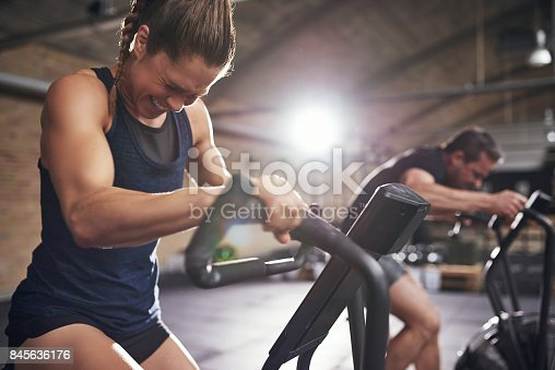 istock Sportsmen working out hard on cycling machines 845636176