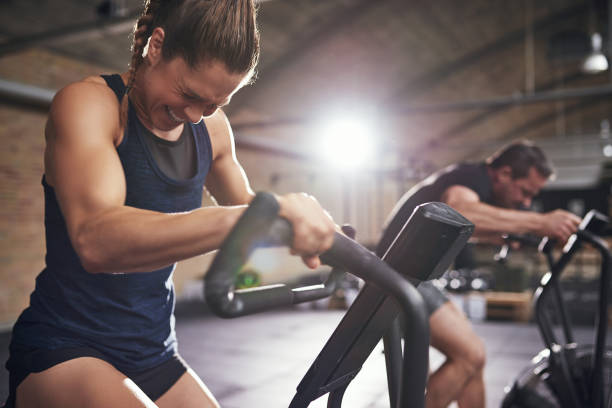 Sportsmen working out hard on cycling machines stock photo