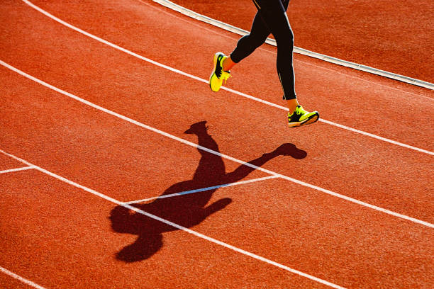 Sportsperson running over the running track stock photo