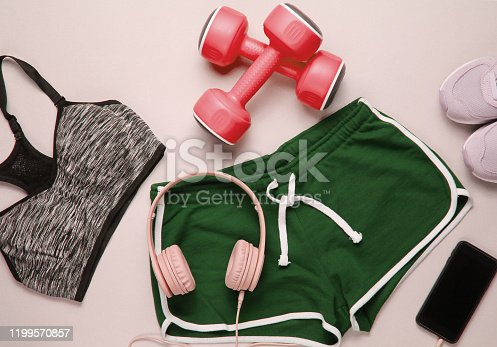 Sportswear and fitness equipment on gray background. Smartphone with headphones, plastic dumbbells, sports bra, shorts, sneakers on gray background. Top view