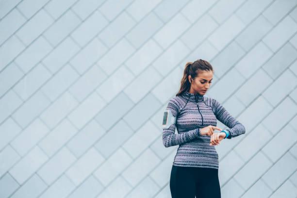 Sportswoman checking her smart watch stock photo