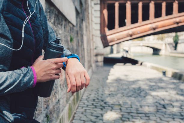 Sportswoman checking pulse on smart watch Close up of woman using smart watch fitness tracker stock pictures, royalty-free photos & images