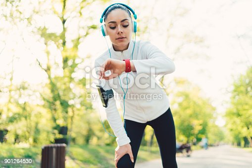 Young woman sports training in the park and checking pulse on smartwatch