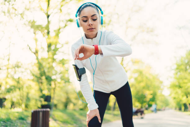 Sportswoman checking pulse Young woman sports training in the park and checking pulse on smartwatch fitness tracker stock pictures, royalty-free photos & images