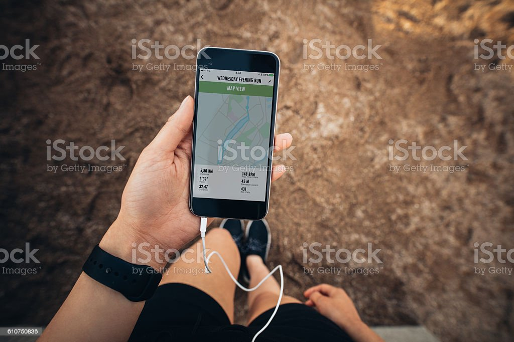 Sportswoman checking smartphone after jogging stock photo