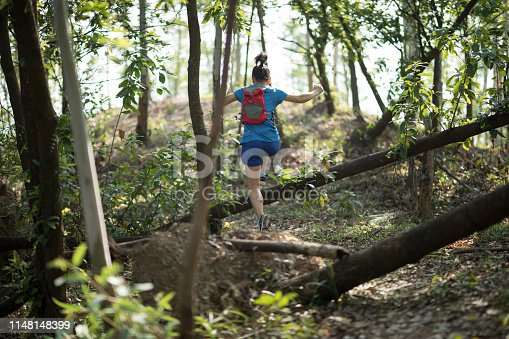 Sportswoman cross country trail running in forest