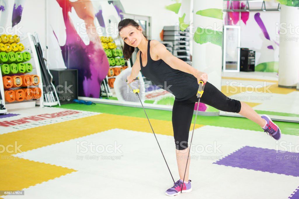 Sportswoman doing exercises with a resistance band in a gym. stock photo
