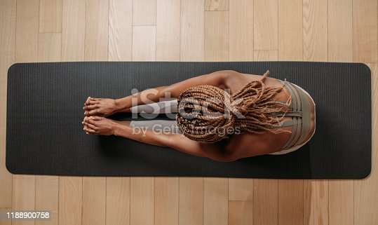 Overhead photo of sportswoman doing stretching exercise on fitness mat.