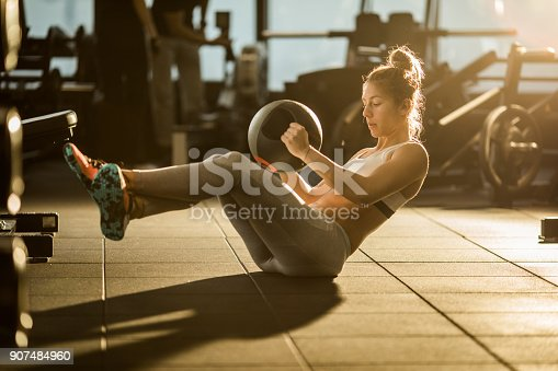istock Sportswoman doing sit-ups with medicine ball on sports training in a gym. 907484960