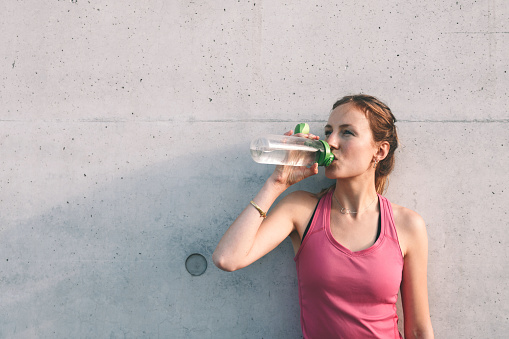 sportswoman drinking from water bottle in front of concrete wall after running