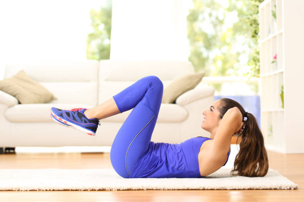 Sportswoman exercising abs doing crunches at home stock photo