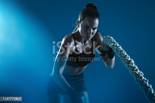 istock Sportswoman exercising with battling ropes 1147772622