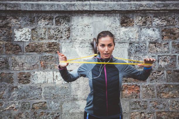training mit widerstand band sportlerin - armband i gummi stock-fotos und bilder