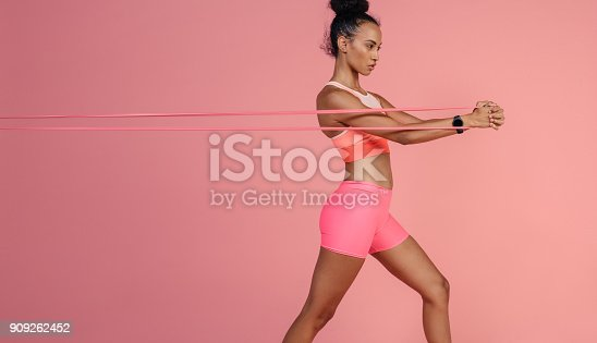 istock Sportswoman exercising with resistance band 909262452