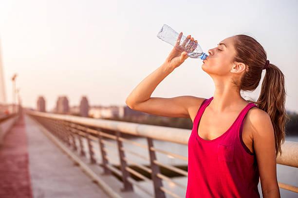 Sportswoman hydrating on the bridge stock photo