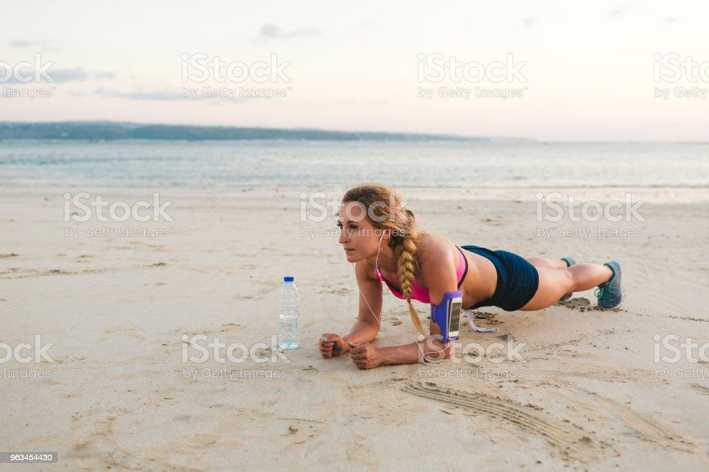 Kulaklıklar içinde sporcumuz ile smartphone omuz çantası ve şişe suyu kum plajındaki tahta yapıyor - Royalty-free Aktif Hayat Tarzı Stok görsel