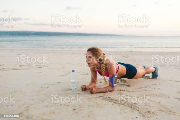 Kulaklıklar Içinde Sporcumuz Ile Smartphone Omuz Çantası Ve Şişe Suyu Kum Plajındaki Tahta Yapıyor Stok Fotoğraflar & Aktif Hayat Tarzı'nin Daha Fazla Resimleri