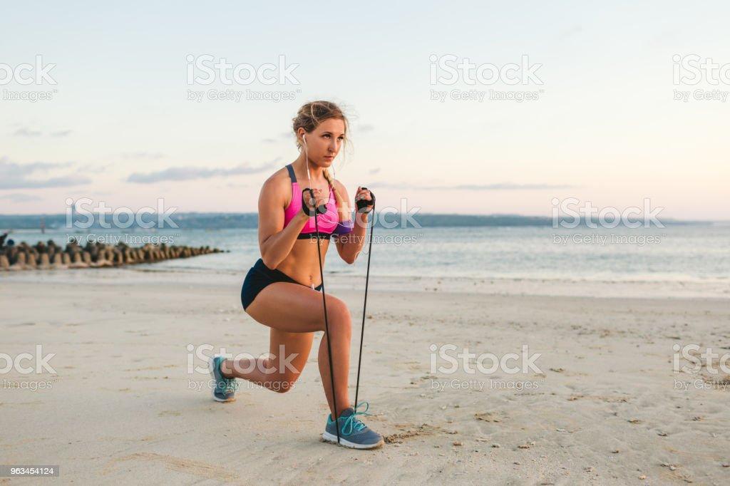 Kulaklıklar içinde sporcumuz ile sahil bandında germe ile egzersiz yaparak omuz çantası içinde smartphone - Royalty-free Aktivite Stok görsel