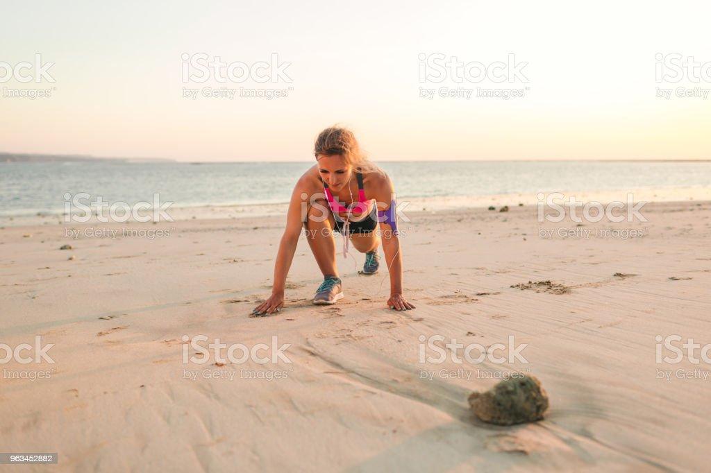 sportive dans les écouteurs avec le smartphone en Étui bracelet exercer sur la plage de sable avec la mer derrière - Photo de Activité libre de droits