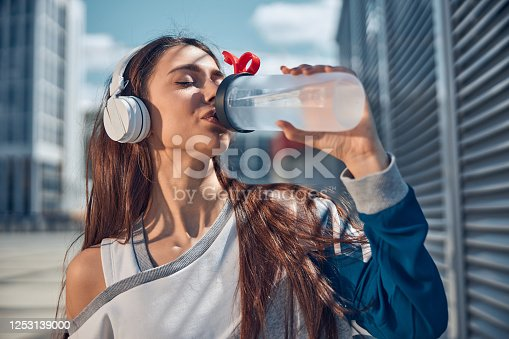 Close up portrait of a young long-haired stylish female drinking water with her eyes closed outdoors