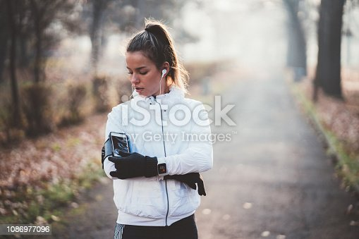 Young woman starting mobile app for sports training before jogging