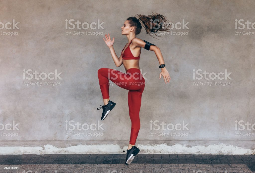 Sportswoman jumping and stretching stock photo