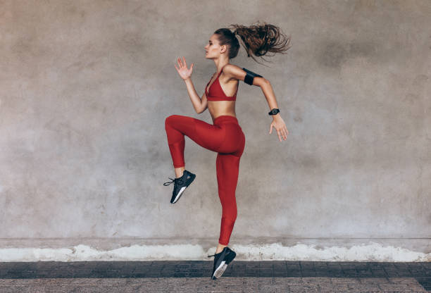 sportswoman jumping and stretching - woman muscular stock photos and pictures