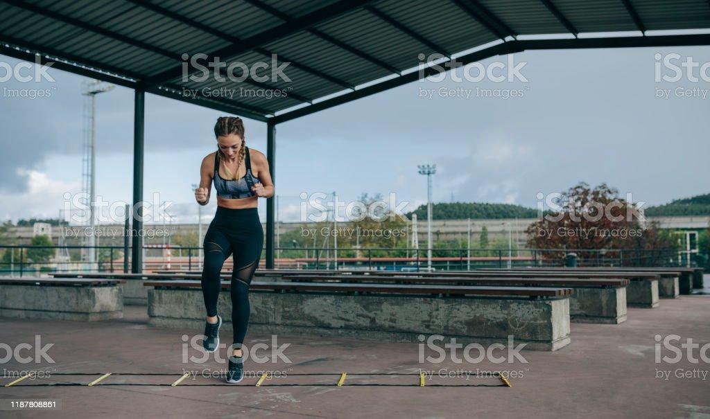 Sportlerin springt auf einer Agilitätsleiter - Lizenzfrei Aktiver Lebensstil Stock-Foto