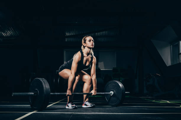 スポーツウーマン持ち上げるバーベル - ウエイトトレーニング ストックフォトと画像